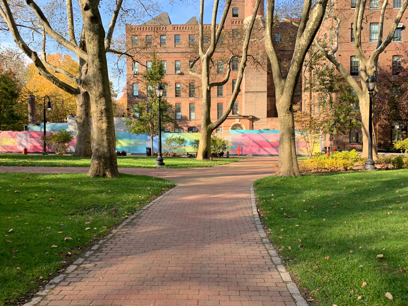 A view from afar of the GenZ installation on the Pratt Brooklyn campus. Brick paths wind through green grass. Some large trees are in the foreground and a large brick building is behind the installation. The installation is a fencing cover and is bright with neon gradients.