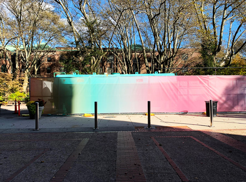 A side view of the GenZ installation on the Pratt Brooklyn campus. The installation is a fencing cover and is bright with neon gradients.