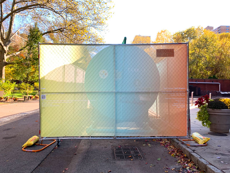 A view of one of the ends of the GenZ installation on the Pratt Brooklyn campus. The installation is a fencing cover and is bright with neon gradients.