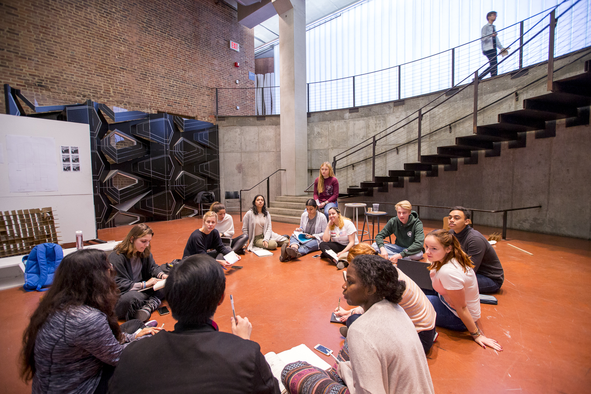 Group photograph of a professor and students sitting in a circle on the ground at Higgins Hall