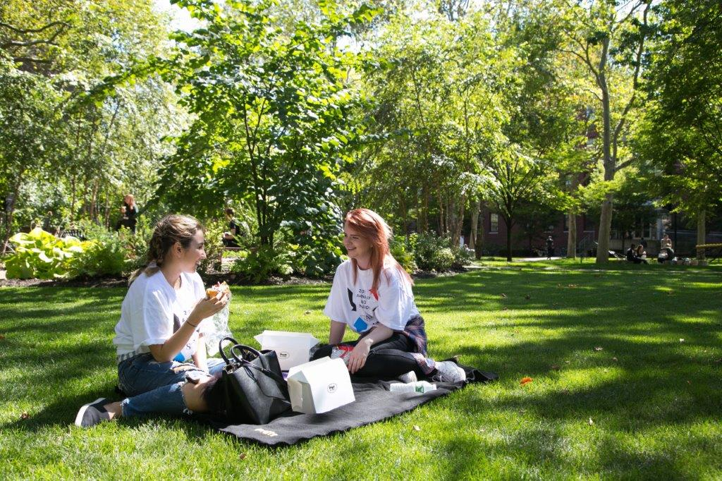 Two students sitting on the grass on the Pratt Institute campus