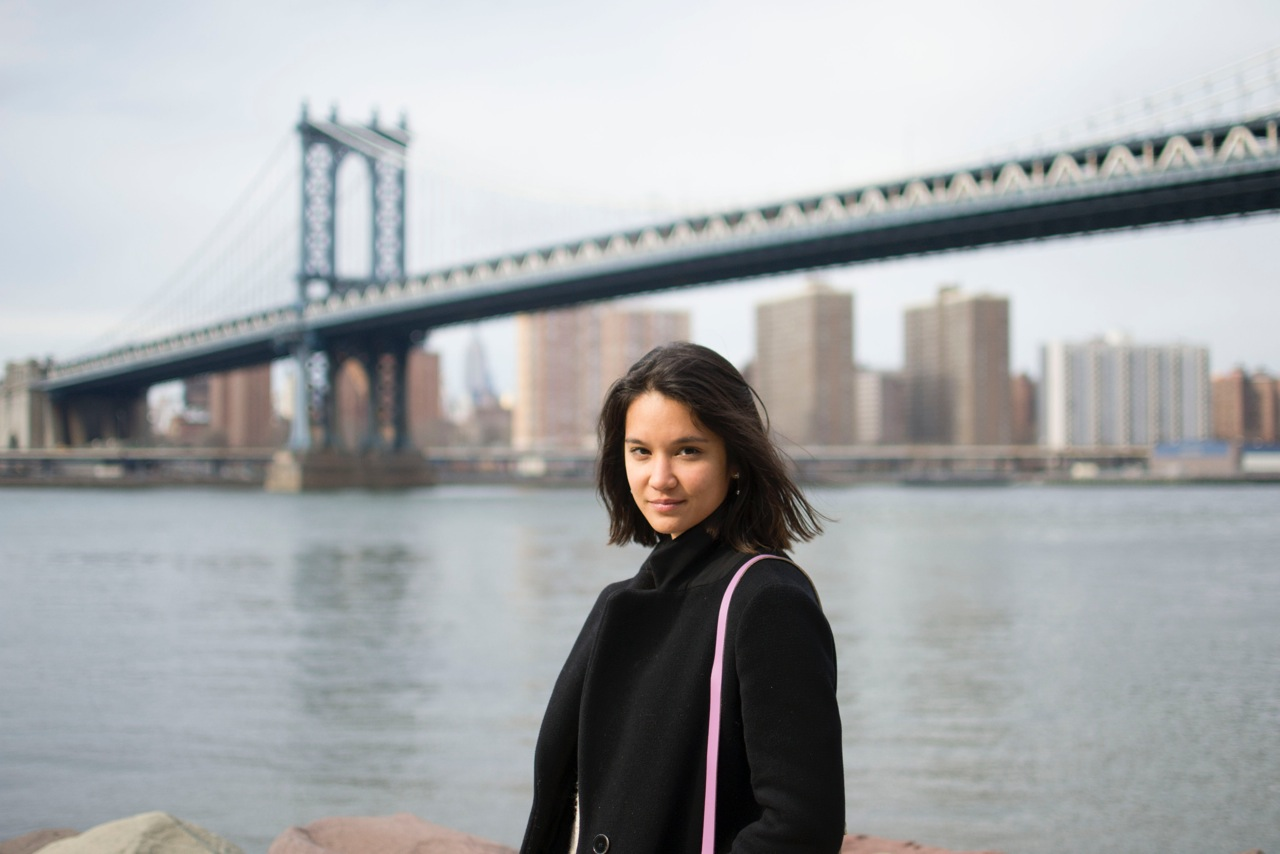 A woman wearing a black jacket looks directly into the camera. The Manhattan bridge, the East River, and Manhattan are in the background.