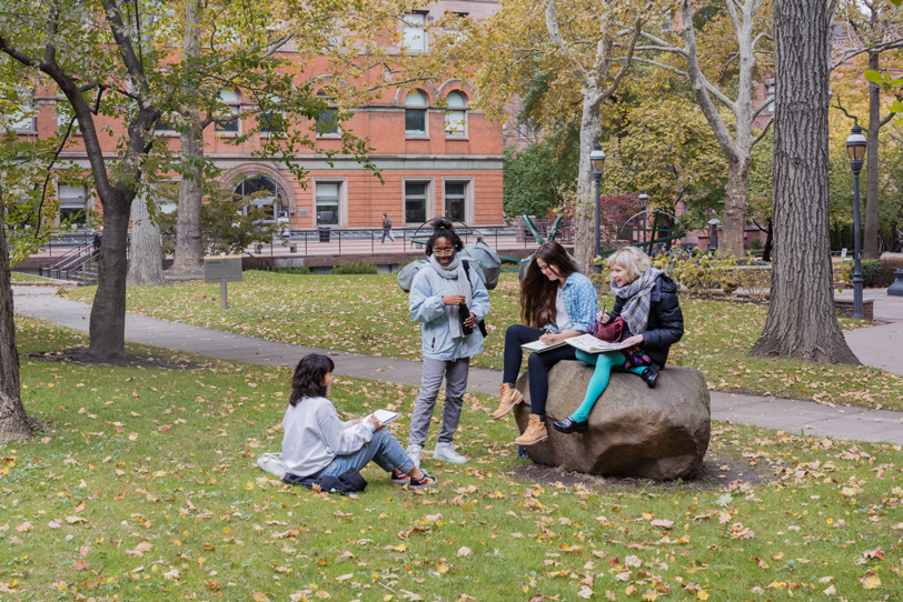 Photograph of four students talking in front of the Brooklyn library