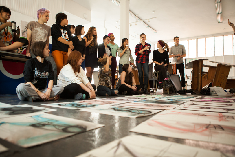 Photograph of a class gathering around and examining artwork on the ground