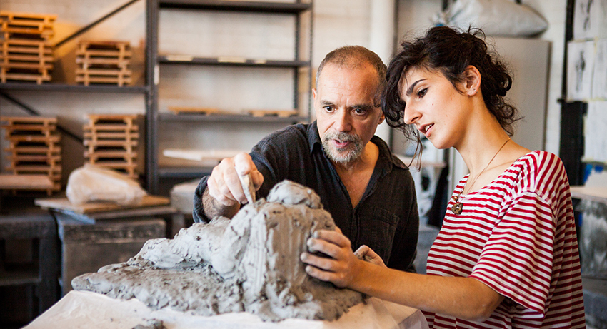 A professor talking to a student about a sculpture