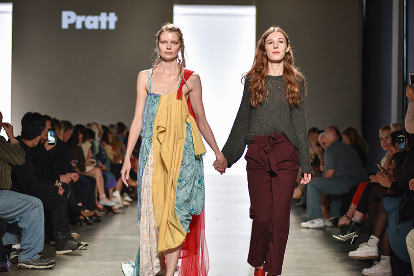 Mila Sullivan walks the runway with a model wearing one of her looks at Pratt Shows: Fashion | The Work in May 2017(photo: Fernando Colon)