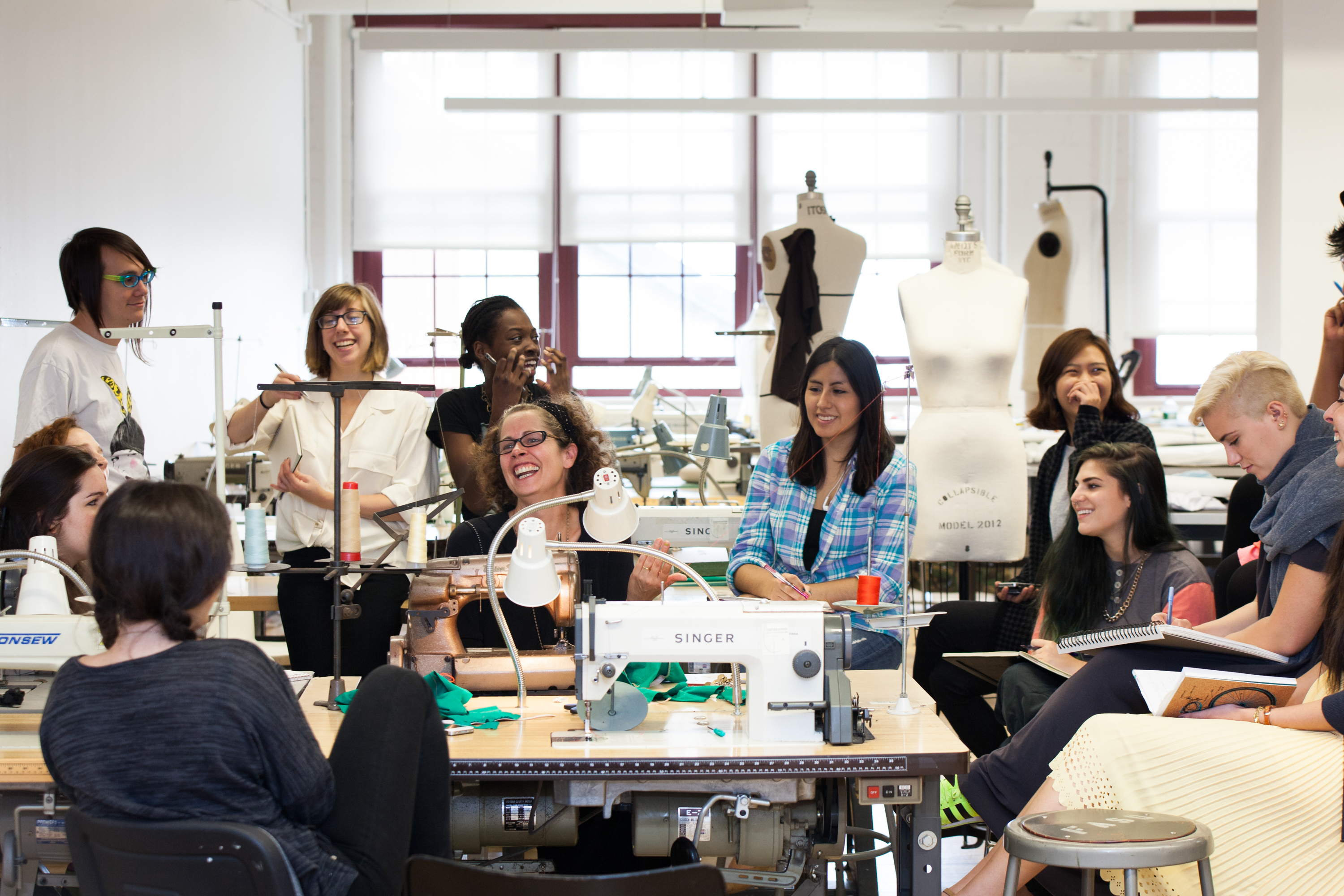 Group photograph of a class having a discussion in a fashion studio