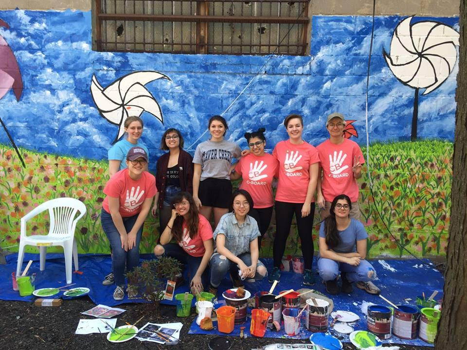 Pratt students in front of a mural