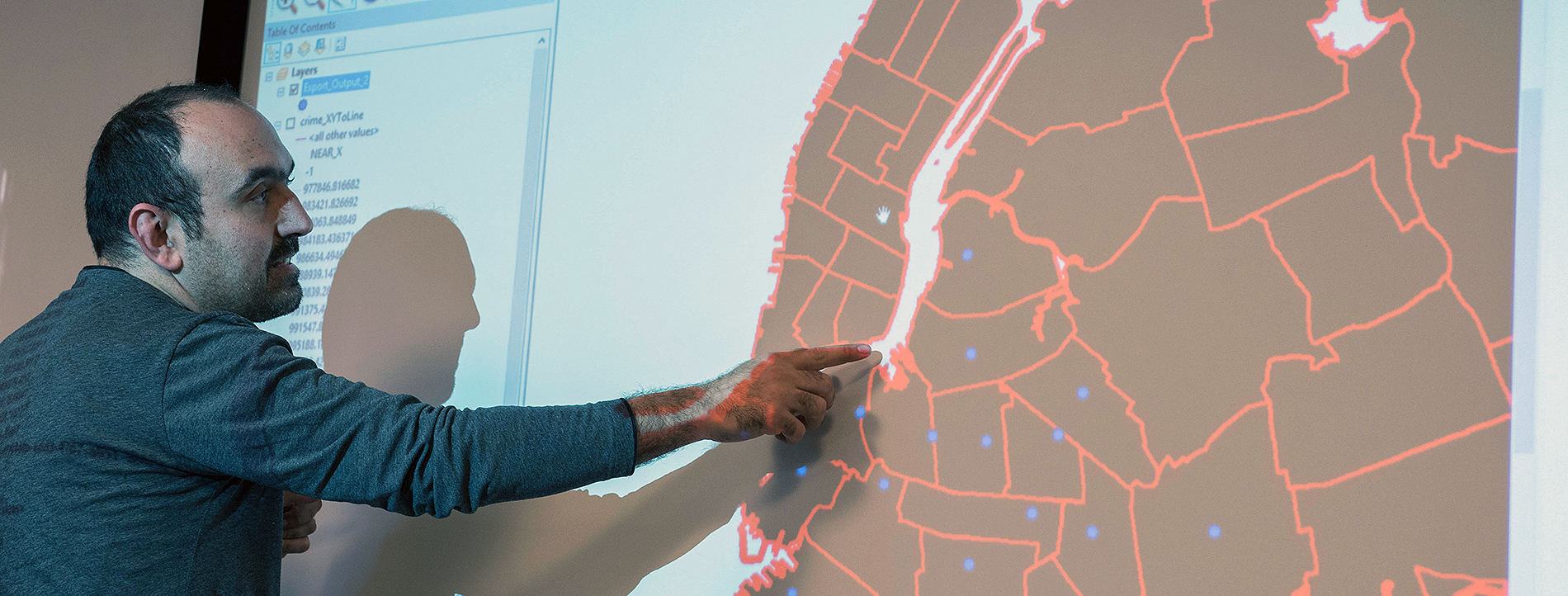 Member of Pratt faculty indicating a place on a map, on a presentation