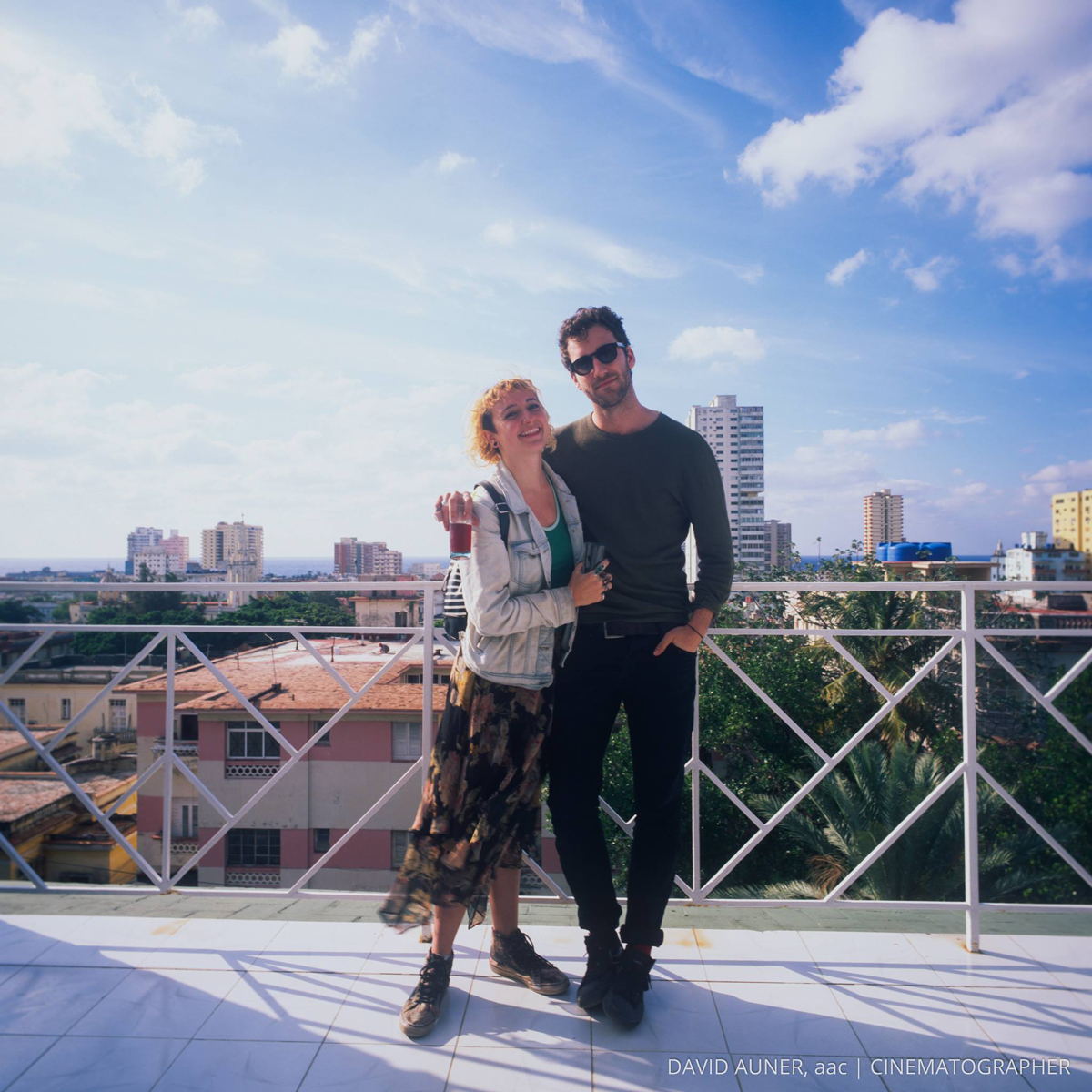 Kylie Shaffer and Charlie Cole standing together on a rooftop balcony with a big blue sky and buildings and trees behind them.
