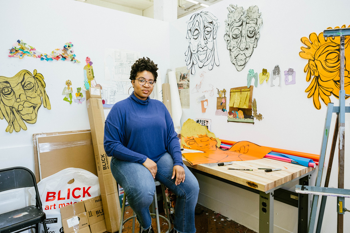 Devin Alexander sitting on a stool in her studio surrounded by her artwork.
