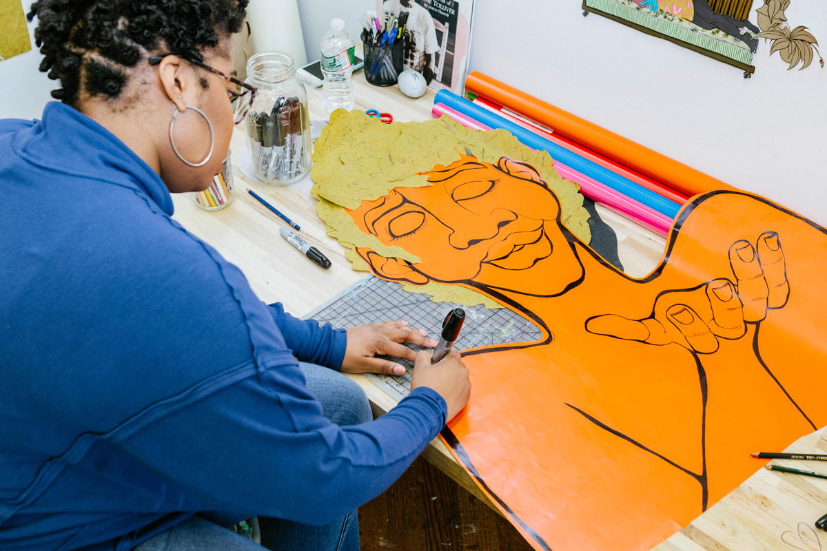 Devin Alexander in her studio working on a drawing. The drawing is a cutout that is in the shape of a person.
