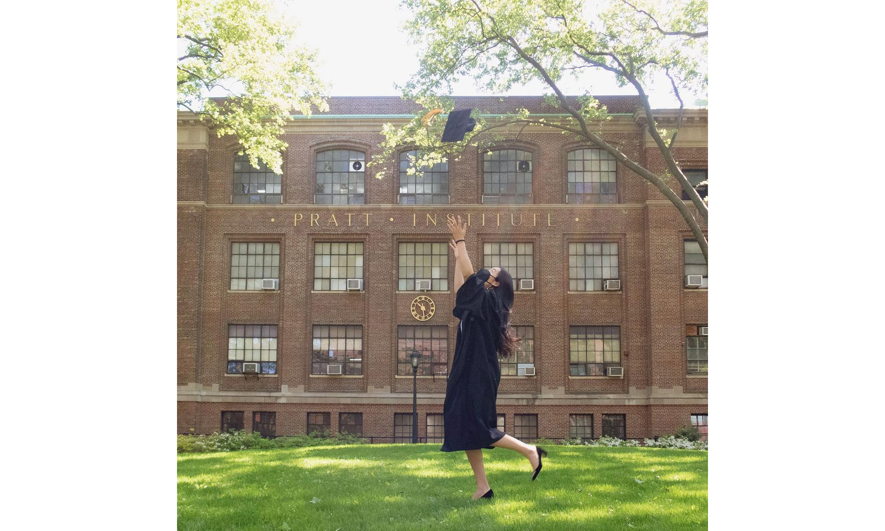 A Pratt graduate in her graduation gown is on campus and throwing her graduation cap into the air