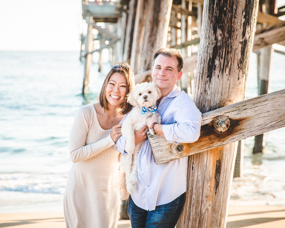 Cynthia Kwan Knotz and Christopher Knotz standing by a pier smiling. Christopher is holding their small white dog.