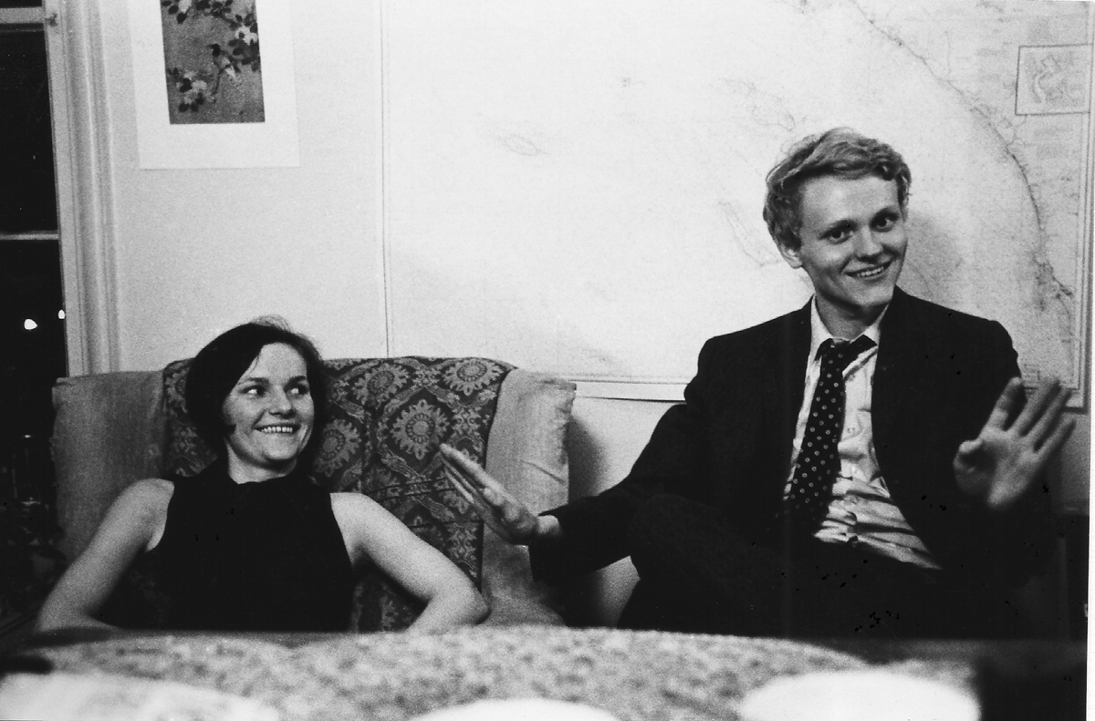 Longia smiles at Bill as he's gesturing with his hands, smiling.