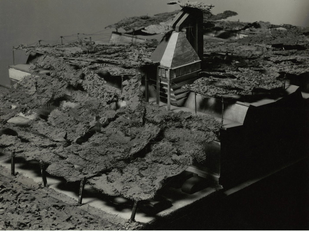 """Model Factory After Camouflage with nets simulating ground. Note: Sloping nets extend beyond actual building to hide shadow parking lot and R. R. siding are considered as well as building itself.,"" created by Pratt Institute and exhibited in the Museum of Modern Art's Camouflage for Civilian Defense, A Circulating Exhibition (1943) (courtesy Pratt Institute Archives Image Collection)"