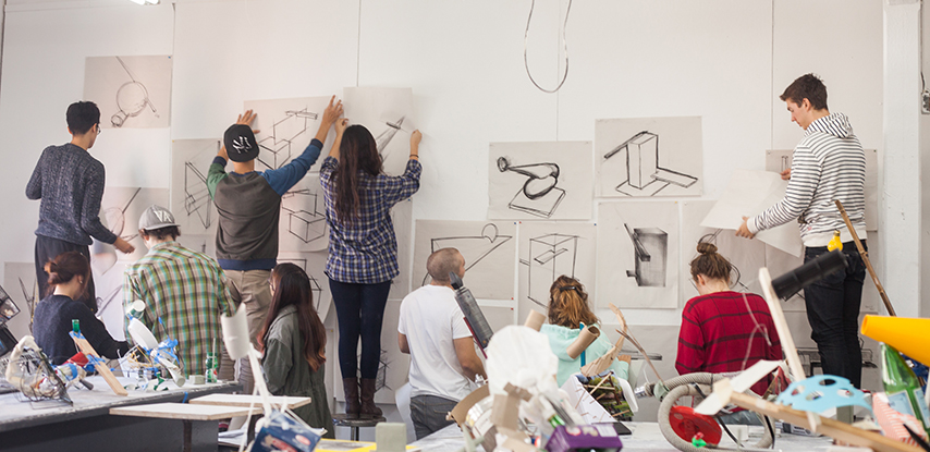 Pratt students placing drawings on the wall, in a workshop or exhibition space