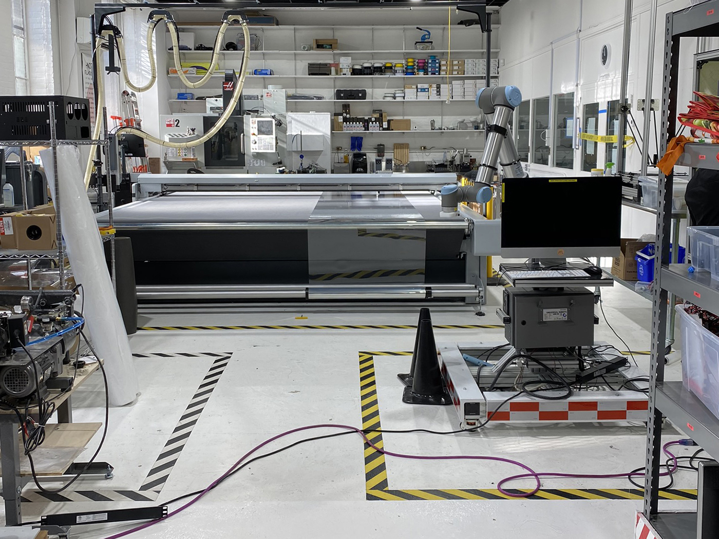 Roll feed setup with the Zünd digital cutter for the non-stop automatization of cutting shields for attachment to a 3D-printed visor (photo by Scott Sorenson)