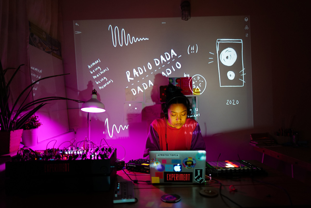 Artist Ari Melenciano behind laptop in studio lit by purple light and projection with squiggles and words
