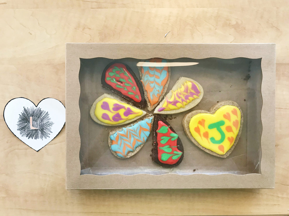 Paper drawing next to the finished baked cookies of participant