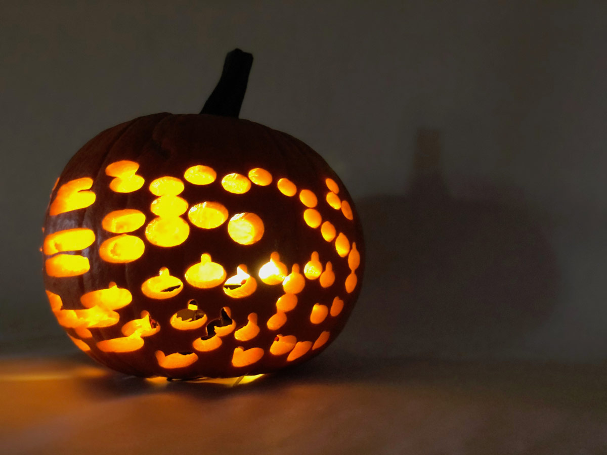 a pumpkin with multiple, small carvings that is lit from within