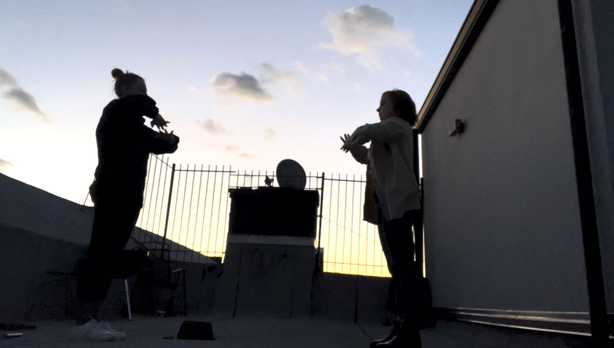 Two women dancing on a rooftop