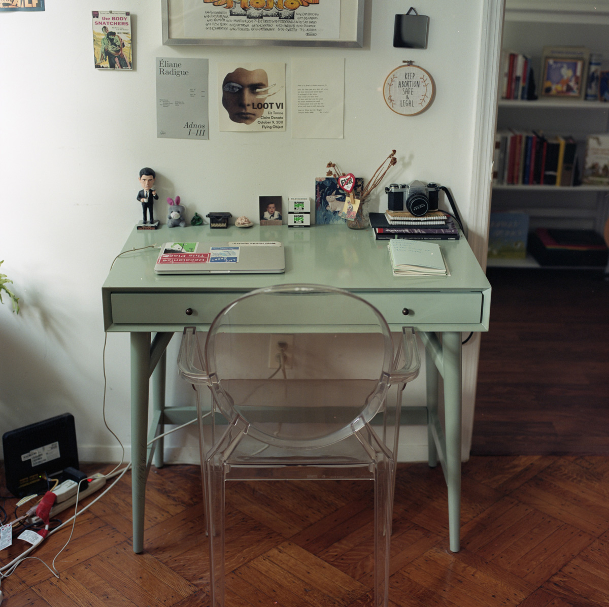 Clear plastic chair pulled up to mint-colored writing desk with sticker-covered laptop, figurines, pictures, notebooks, camera
