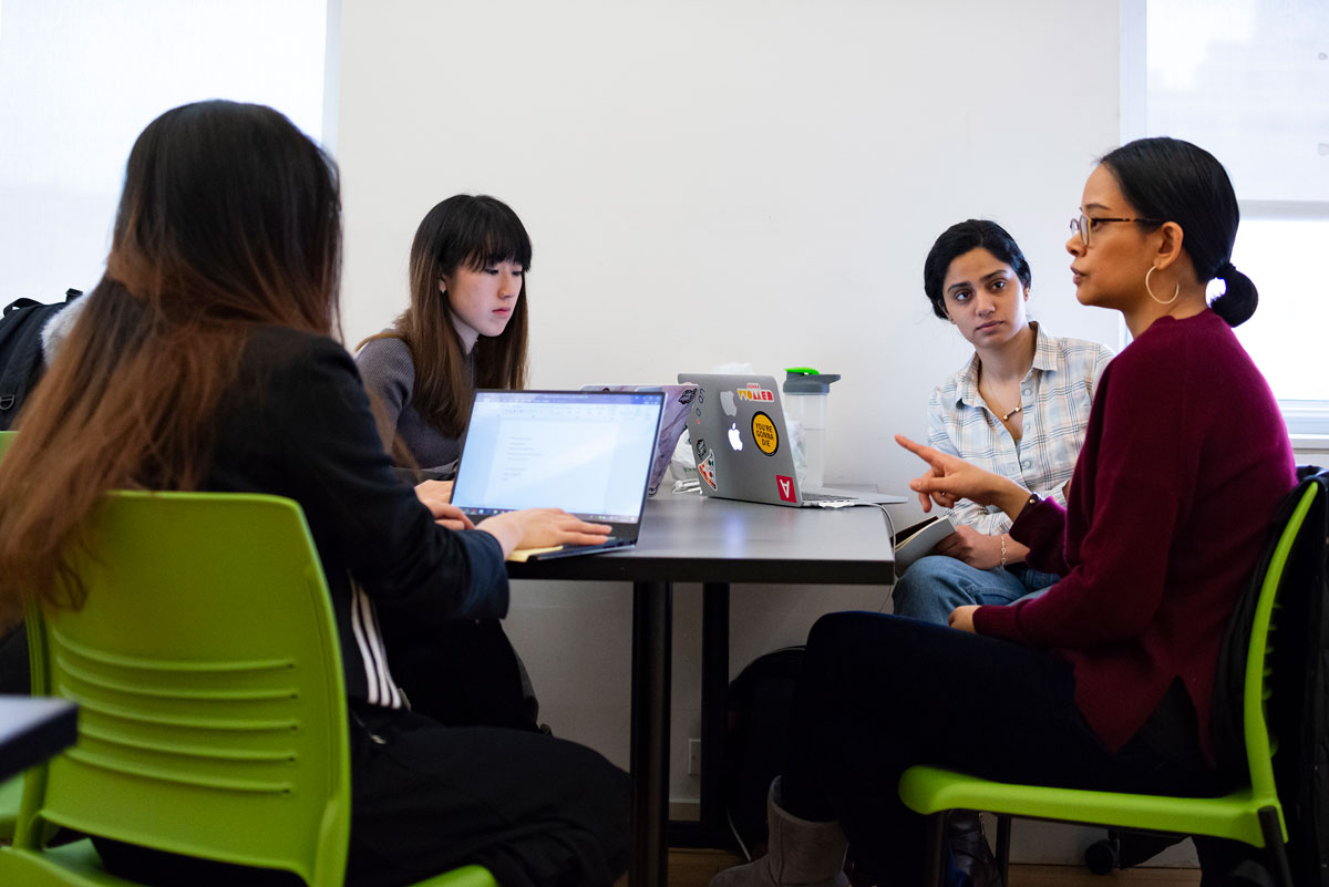 A team of students seated at a table, discuss their work with a client.
