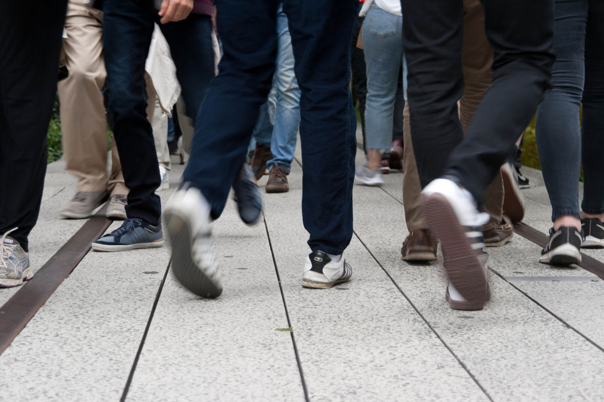 Image of feet walking around a busy, city street