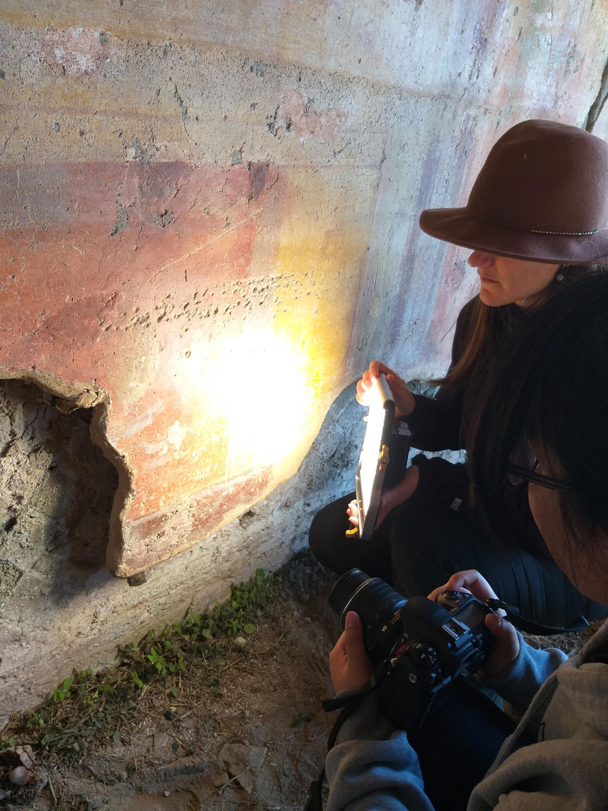 two researchers kneel in front of an ancient wall painting; one holds a camera, one holds a light source.