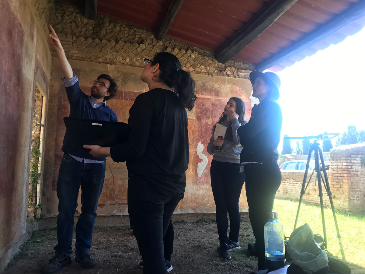 four researchers stand around an ancient wall
