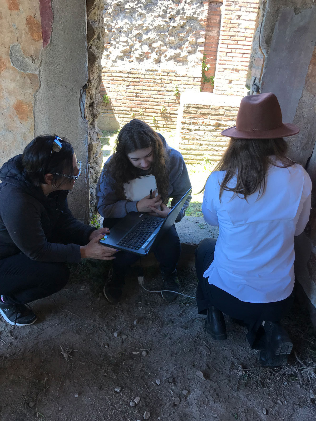 Researchers are crouched next to an ancient wall, looking over data on a laptop