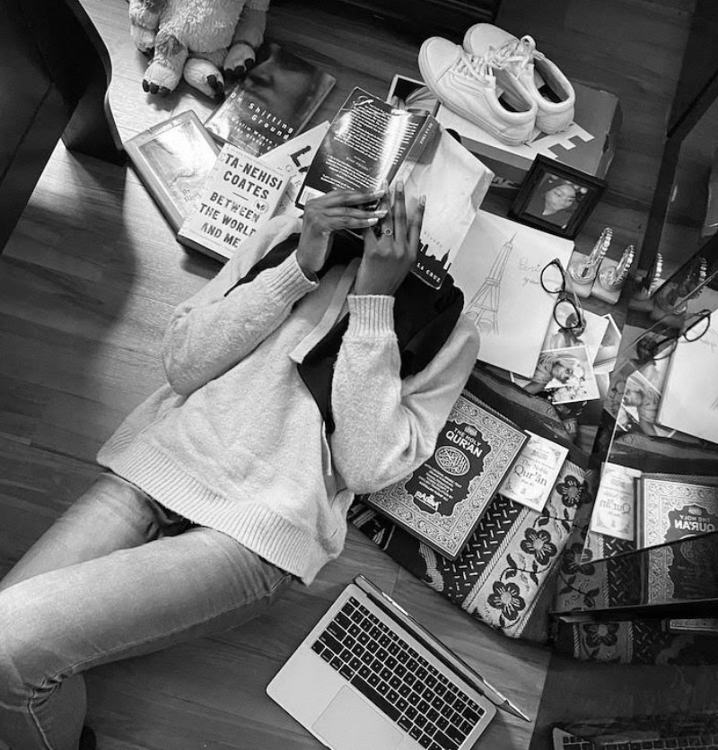 Teenage girl has book over her face, surrounded by objects that are tied to her identity