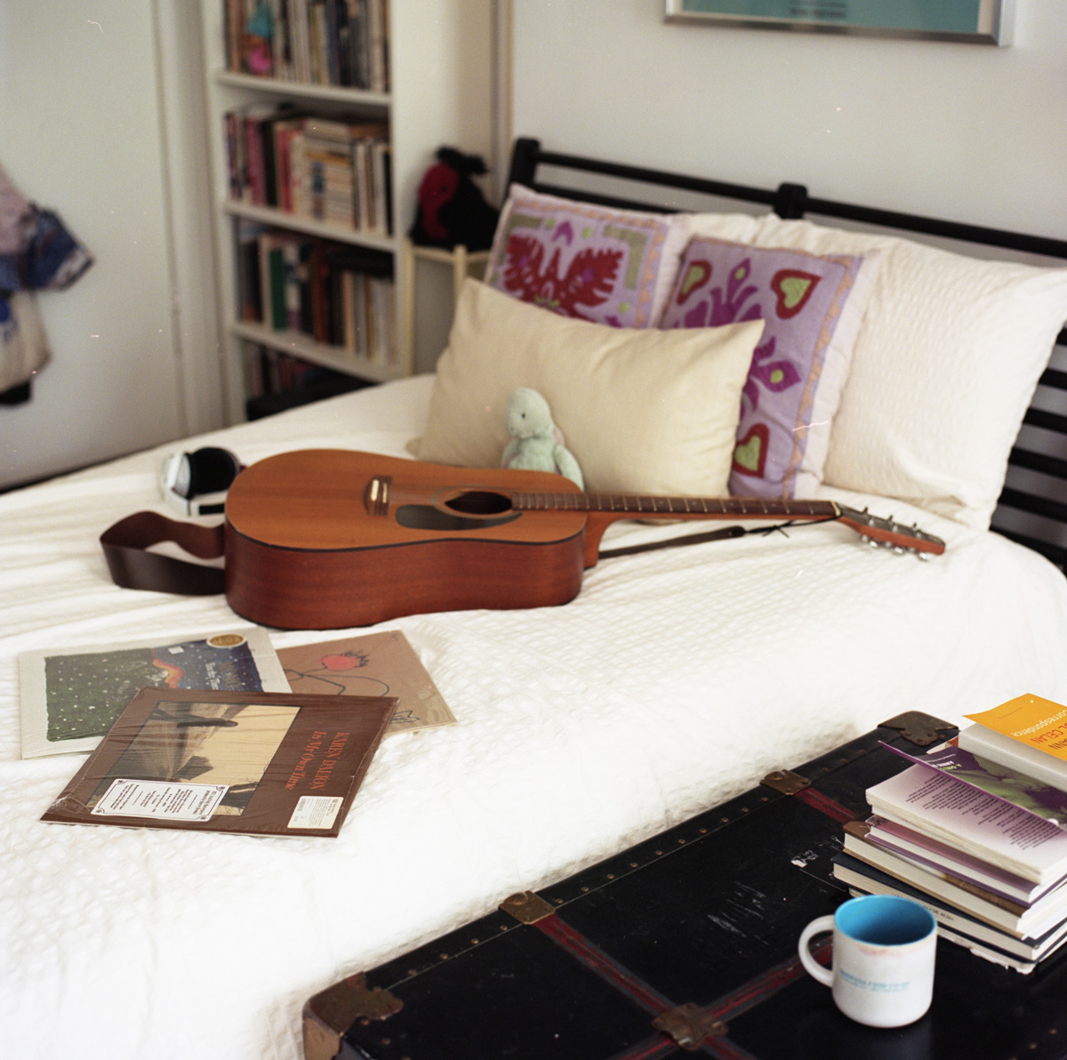 Acoustic guitar laid over white bedspread with three scattered records and stuffed turtle leaned against pillows