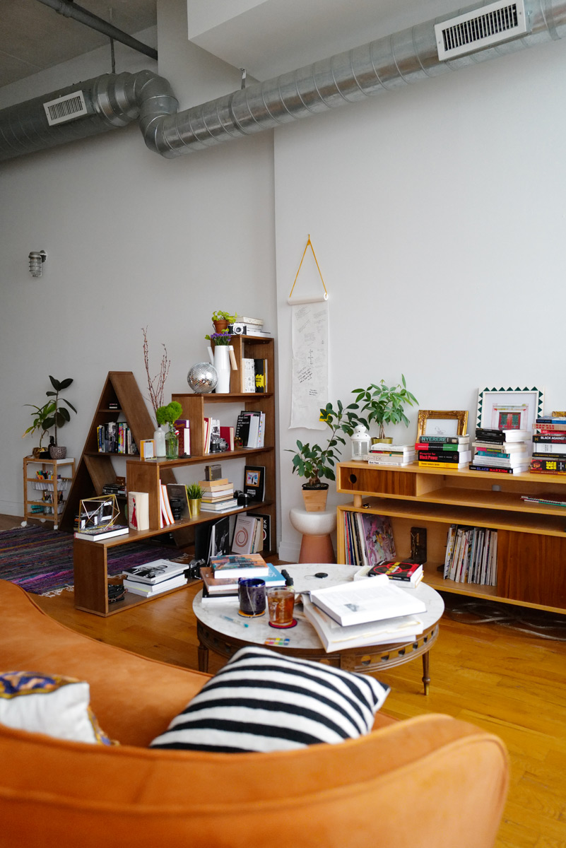 Artist's home studio with bookshelves, cabinet with vinyl records, and coffee table stacked with books