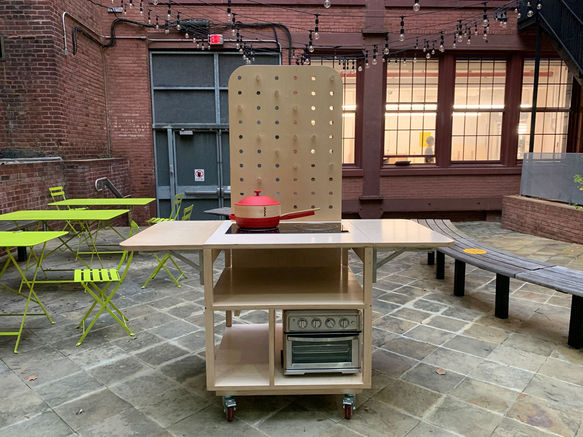 Wooden mobile kitchen cart on casters with a tall pegboard, two induction burners, and a small oven. The cart is in a courtyard surrounded by brick walls. There are string lights and neon green outdoor cafe tables and chairs in the background.
