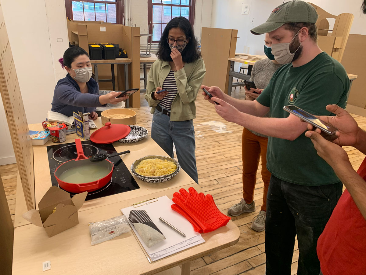 Five graduate students in masks surrounded a mobile kitchen cart, taking photos with their phones of a pile of pasta that has just been cooked on the stovetop.