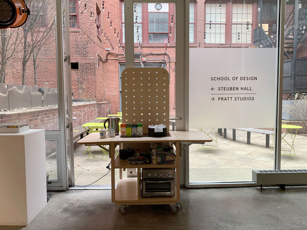Wooden mobile kitchen cart on casters with a tall pegboard and a small oven is parked in front of glass double-doors leading to a courtyard. On the surface of the kitchen are some boxes of tea, a kettle, mugs, and a basket of wrapped baked goods. A vinyl sign on the glass reads,