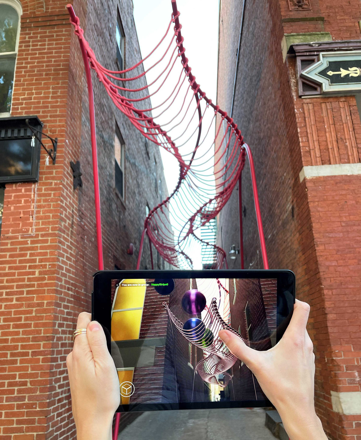 hands hold up an ipad to show the augmented reality of the physical world being captured through the app