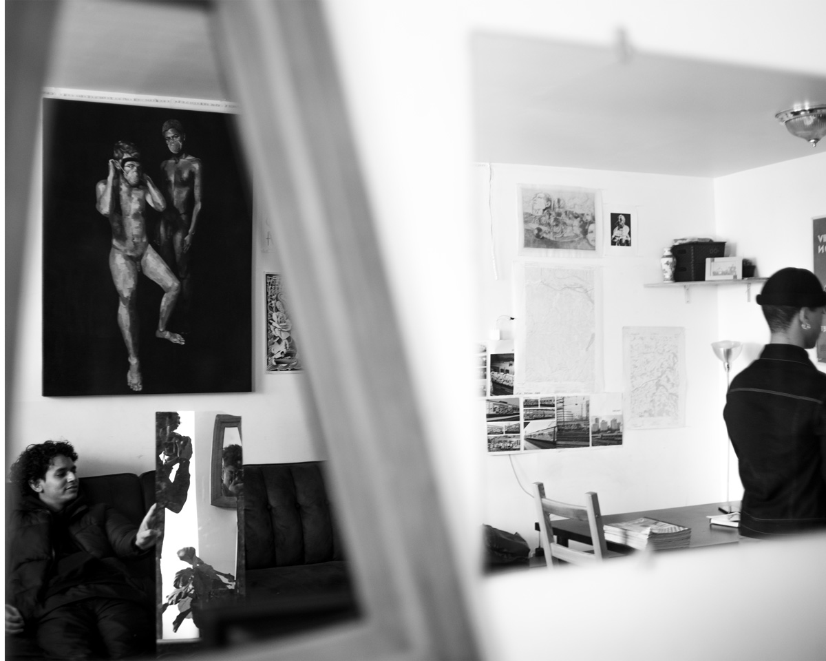 Interior of artwork-filled New York apartment with two art school students, and photographer captured in mirrors