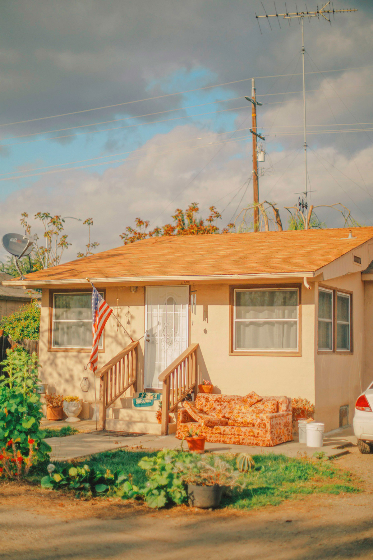 Clay-colored house bathed in sunlight under clouds, with outdoor sofa, US flag, windchimes, satellite dish, and potted garden