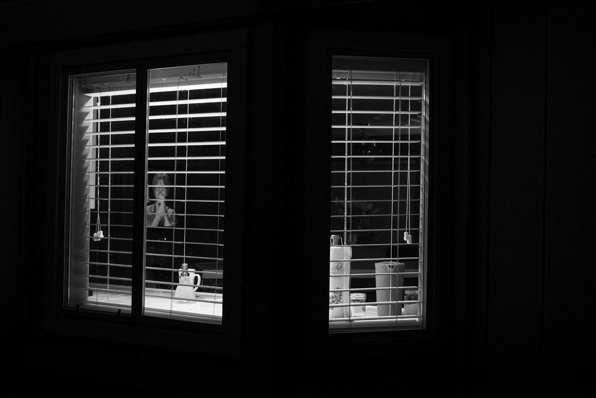 Nighttime view from outside darkened house through kitchen windows, with television image behind open blinds