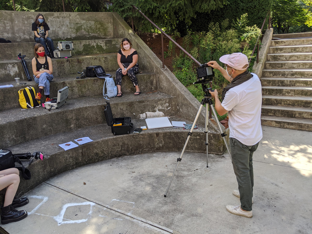 Four masked students sit on different levels of Pratt's outdoor amphitheater. Each has photo equipment next to them. They are watching a masked professor give a demonstration on a tripod-mounted camera.