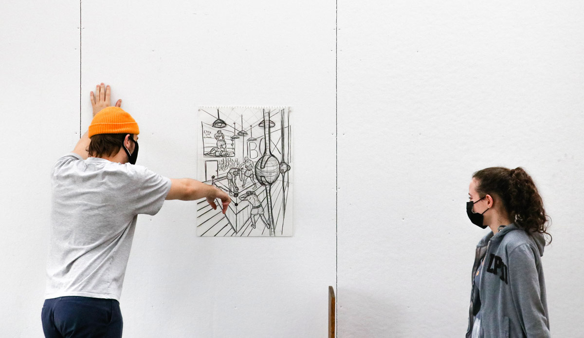 Two students are looking at a sketch of a boxing gym that has been mounted to the wall. The student on the left is leaning in towards the sketch and is pointing at something in the work.