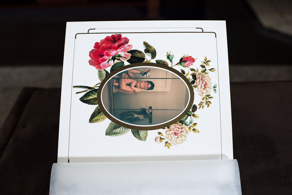Page of photo album viewed from the side, with snapshot, encircled by illustration of flowers, of parent and child in mirror