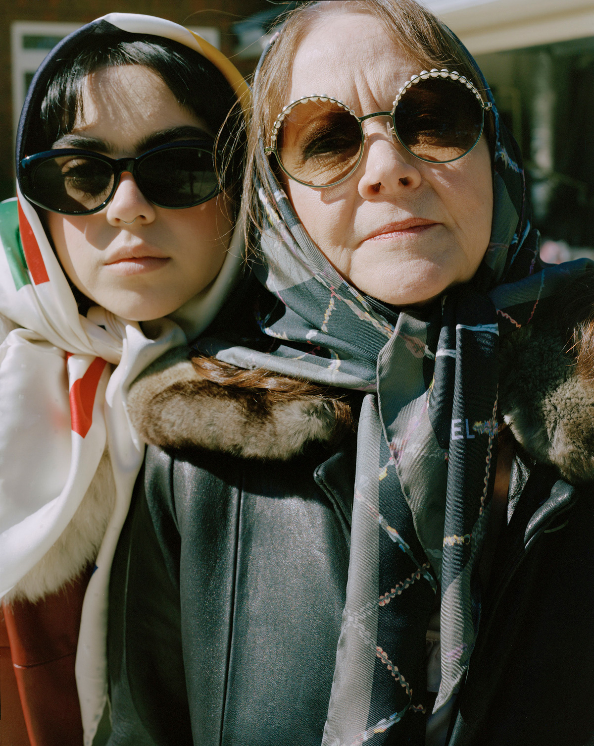 Mother and daughter side by side outdoors wearing vintage-looking sunglasses, silken headscarves, and fur-collared coats