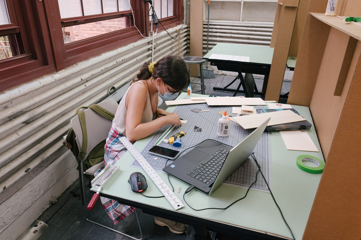 A masked student in a studio works on a project on a cutting mat. They are using different tools to measure, cut, and glue. There is a computer on the desk with them as well as some scraps of material.