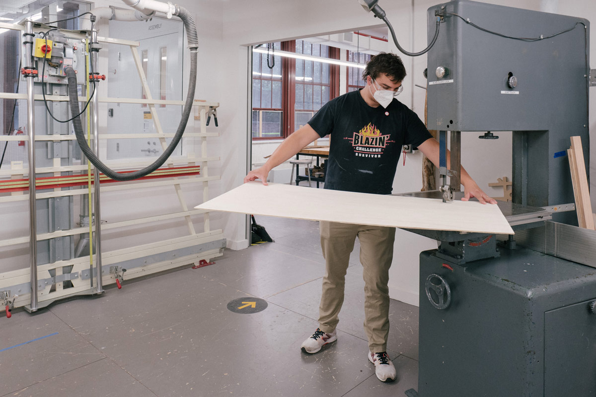 A masked student in the woodshop guides a piece of wood through a power saw.