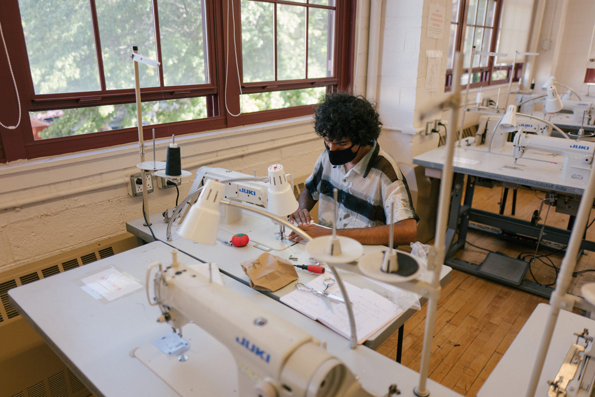 A student wearing a mask operates a sewing machine within a workshop. There are other sewing machines at other desks around him.