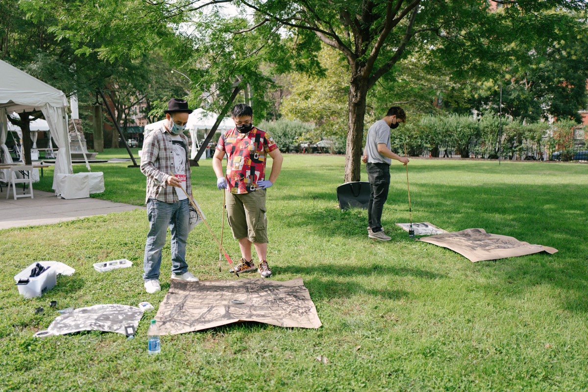 Three students wearing masks are working on paintings that are laying in the grass outside on campus.